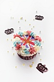 A cupcake topped with butter cream and a Union Jack surrounded with chocolate crowns