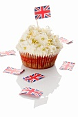 A cupcake decorated with golden beads and a Union Jack