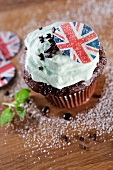 A chocolate cupcake topped with mint cream and a Union Jack