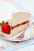 A slice of sponge cake filled with strawberry jam