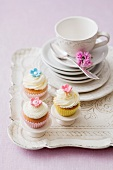 Three cupcakes with a stack of plates and a teacup