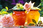 Two jars of jam with roses and rose hips