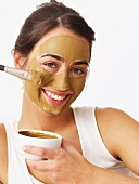 Woman applying healing earth face mask