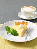 A slice of lemon tart and a cup of cappuccino