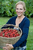 Woman carrying basket of cherries
