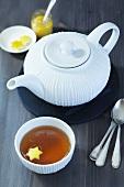A tea pot, a bowl of tea with a piece of star-shaped lemon zest