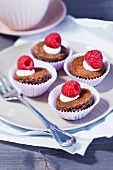 Round sponge cake topped with cream and raspberries on a plate