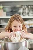 A little girl kneading dough in a mixing bowl