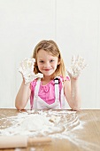 A little girl showing hands covered in dough