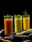 Three different vegetables soups in glasses with cheese sticks