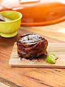 Beef steak wrapped in bacon with a slice of lime