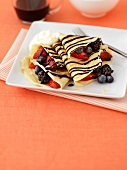 Crêpes filled with berries and chocolate sauce