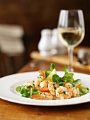 Garlic prawns with lamb's lettuce and a glass of white wine