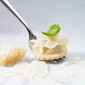 Ravioli, grated Parmesan and basil leaf on a fork