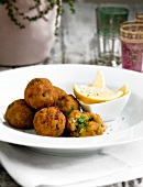 Deep-fried balls of asparagus risotto with lemon wedges