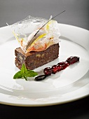 Walnut brownie with baked apple ice cream in a sugar basket served with port wine berries