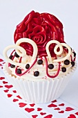 A cupcake decorated with hearts and a red rose for Valentine's Day