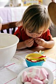 Young girl eating sweets while baking