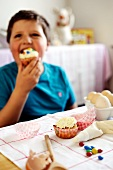 Young boy eating a cupcake