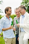Three men with bottles of beer outdoors