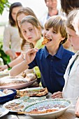 Children standing by a buffet at a garden party