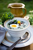 Green cabbage soup with boiled eggs and bacon