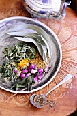 Dried herbs and rose buds with herb tea