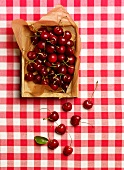 Cherries in a crate on a red and white checked tablecloth