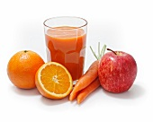 Multi-vitamin juice surrounded by oranges, apples and carrots