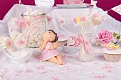 Cake pops, chocolate lollies, marshmallows, a cupcake and biscuits, all in white and pink