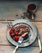 Entrecote with grilled cherry tomatoes on a tin plate
