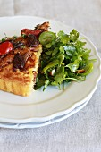A slice of pissaladière with olives, onions and tomatoes, with a side salad