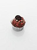 A cupcake decorated with chocolate cream and hearts