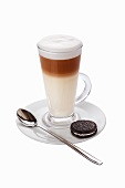 A caffe latte with a chocolate biscuit