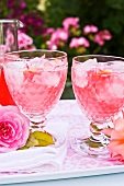 Two glasses of rose syrup with ice cubes and rose petals on a tray