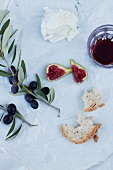 An olive branch, ricotta, red wine, figs and bread