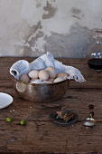 Fresh eggs in an old copper dish on a rustic wooden table