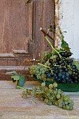 Green and red grapes on a wooden table