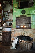 Cat sitting in front of wood-fired, tiled oven in rustic kitchen