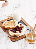 White bread topped with honey and cranberries and peanut butter