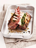 Stuffed lamb loin rack joint in a roasting dish