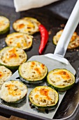 Grilled courgette slices with feta on a baking tray and a spatula