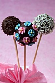 Chocolate cake pops decorated with sugar flowers and light and dark chocolate sprinkles