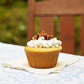 A Vanilla Cupcake with Maple Frosting and Bacon Pieces