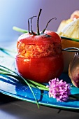 A stuffed tomato filled with toast, onion, raw ham and basil
