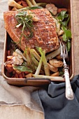 Crispy roast pork on a bed of oven-roasted vegetables in a roasting tin
