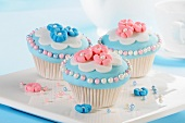 Cupcakes decorated with marzipan flowers and sugar balls