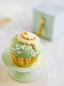 A cupcake decorated with green icing