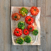 Green and red tomatoes on newspaper