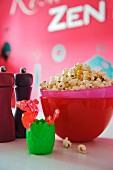 Freshly-made popcorn in pink bowl next to salt and pepper grinders